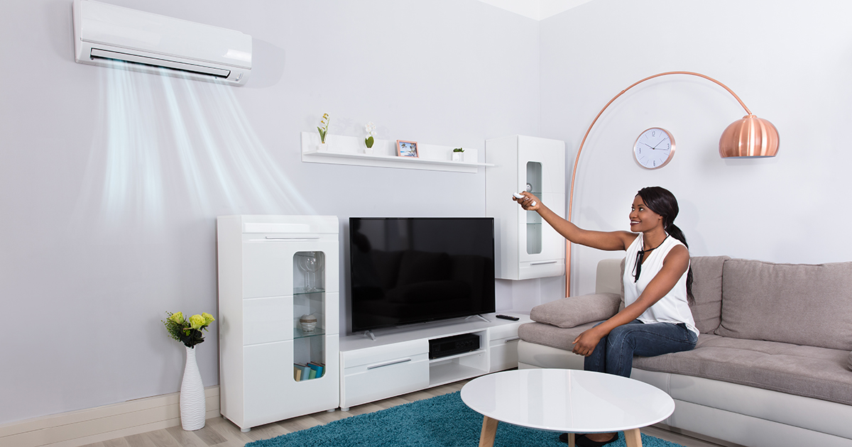 Woman in front of a ductless mini split heating system